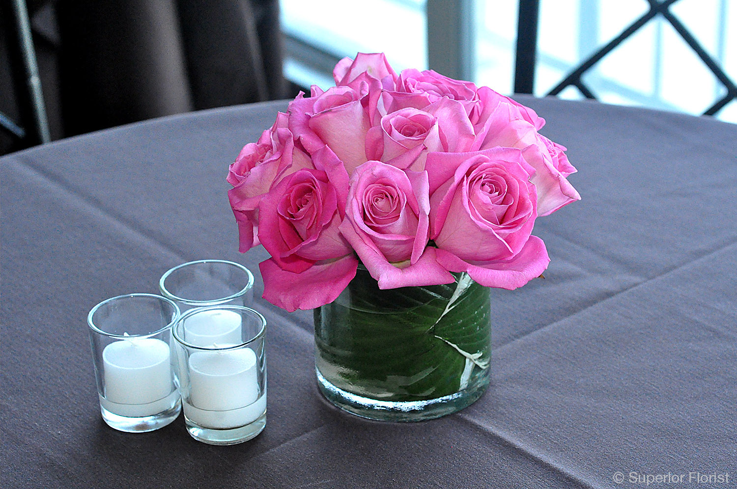 Superior Florist – Cocktail Tables: A simple cocktail table floral arrangement of pink roses in a small, cylindrical glass vase. Leaf wrap lining inside of vase.