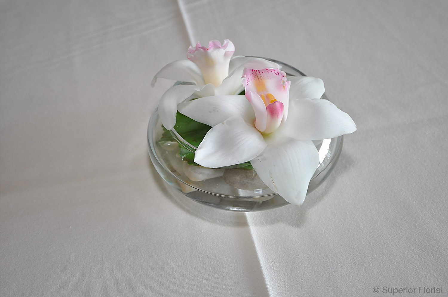 Superior Florist – Cocktail Tables: Floral arrangement of two Cymbidiums floating in a lotus bowl.