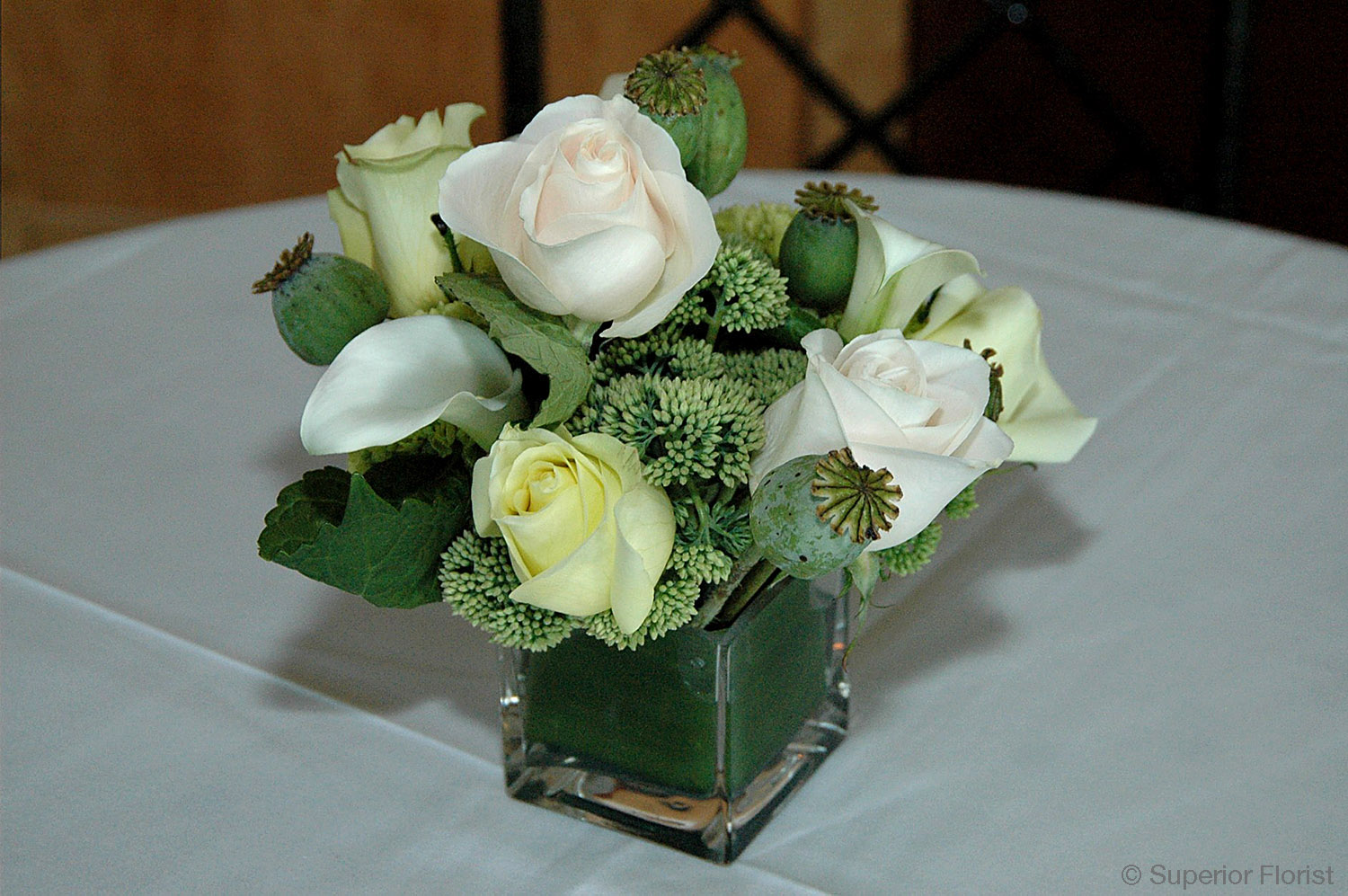 Superior Florist – Cocktail Tables: Floral arrangement of white roses, white mini-Callas, Sedum and poppy pods in clear, glass cube vase. Inside of vase lined with leaf wrap.