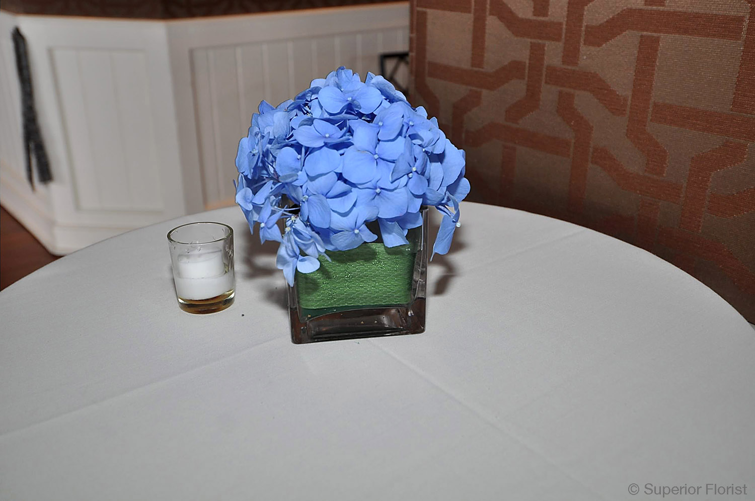 Superior Florist – Cocktail Tables: Floral arrangement of blue Hydrangeas in a small, glass cube vase. Leaf wrap lining inside of vase.