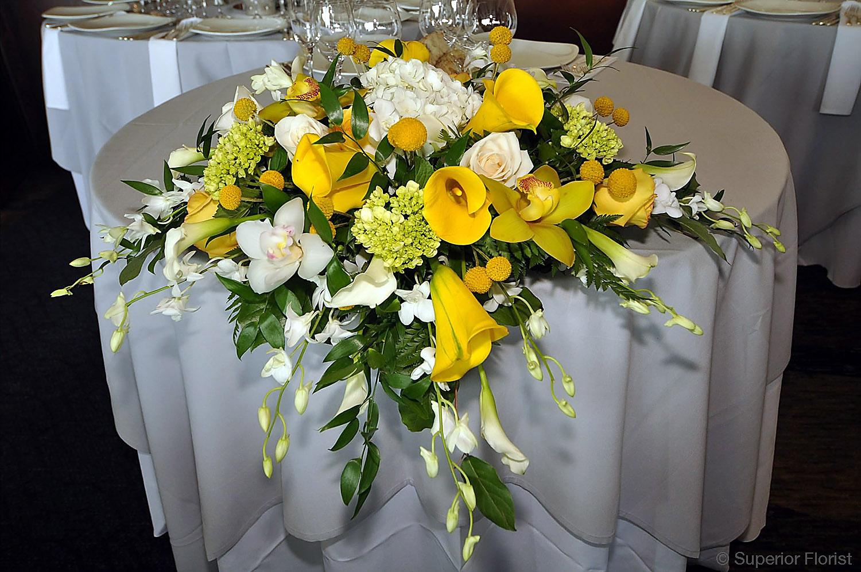 Superior Florist – Sweetheart Tables: Table arrangement of yellow Callas, yellow Cymbidiums, white Hydrangea, mini Callas, Dendrobiums and Craspedias.