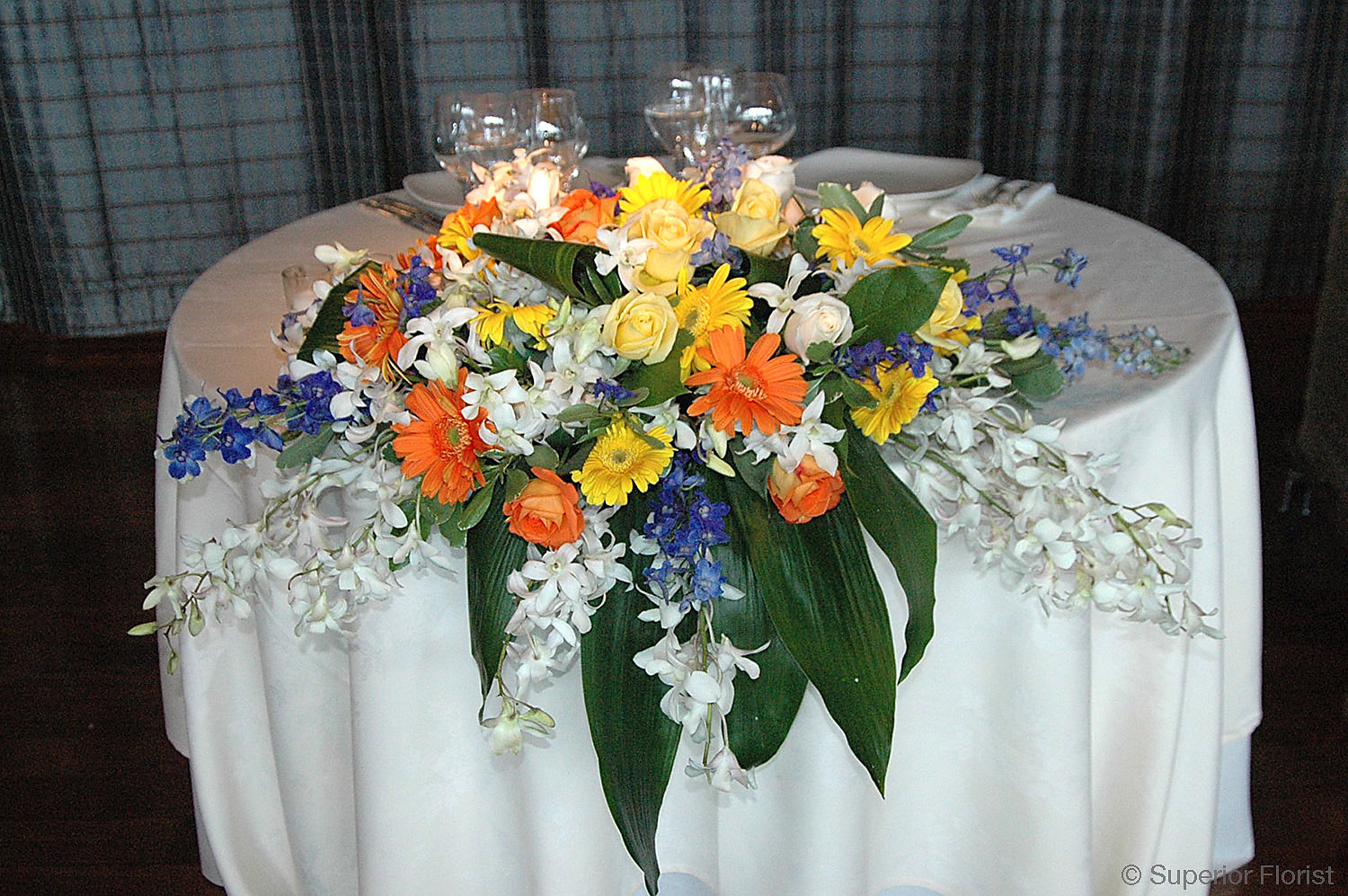Superior Florist – Sweetheart Tables: Arrangement of mixed florals with foliage.