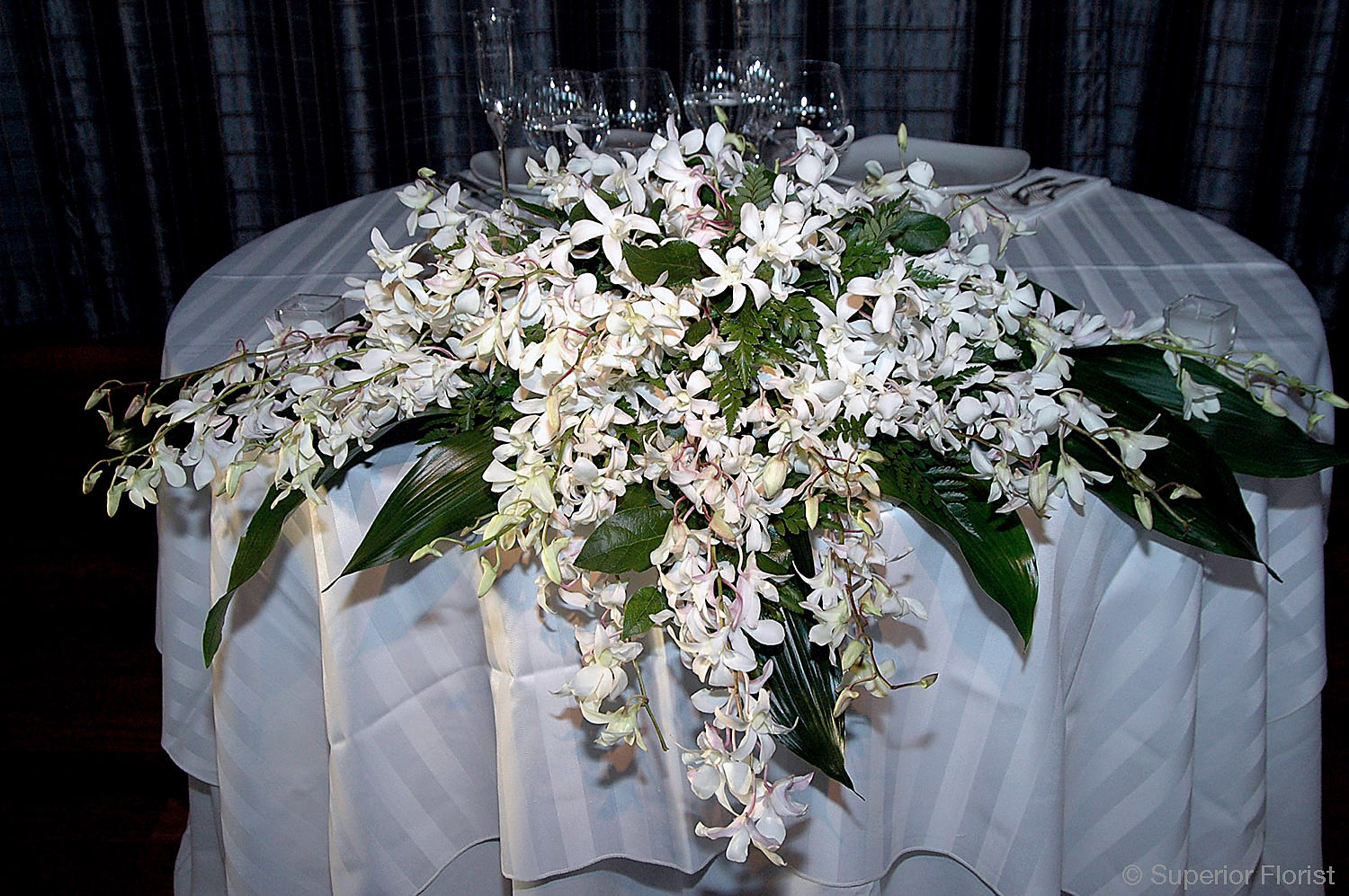 Superior Florist – Sweetheart Tables: Arrangement of cascading white Dendrobium and foliage.