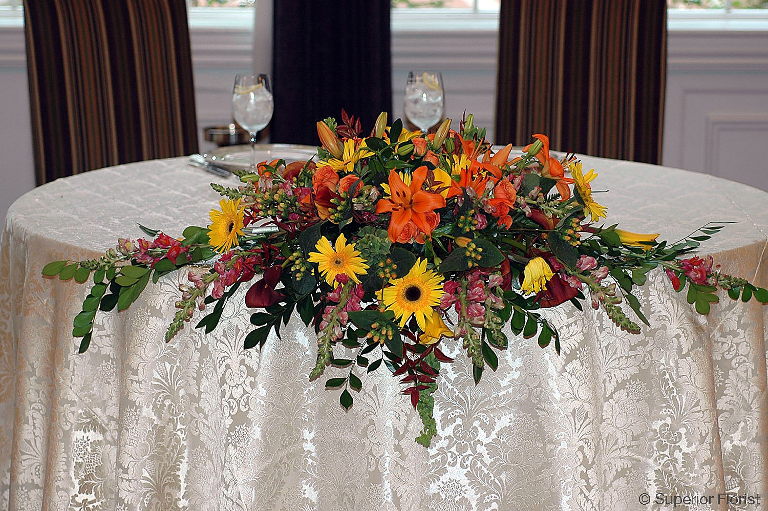 Superior Florist – Sweetheart Tables: Draping arrangement of autumn colored flowers.