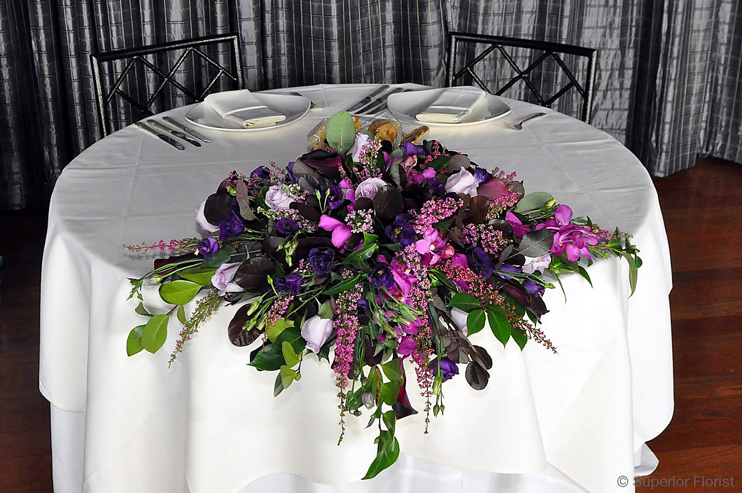 Superior Florist – Sweetheart Tables: Arrangement with shades of pink and lavender, heather, Lisianthus, Callas, Eucalyptus and Dendrobiums.