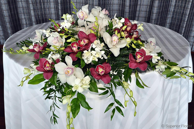Superior Florist – Sweetheart Tables: Arrangement of cascading Cymbidiums and Italian Ruscus.