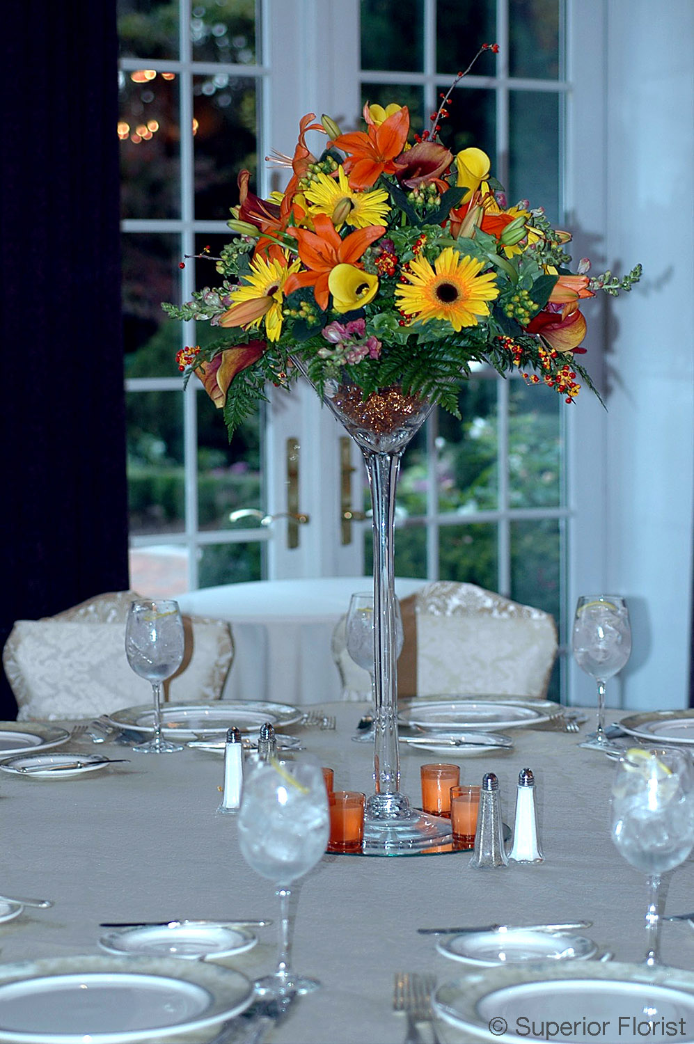 Superior Florist – Centerpieces:  Autumn flowers including Callas, Lilies, Gerberas, Hypericums and bittersweet arranged in a large martini glass vase.