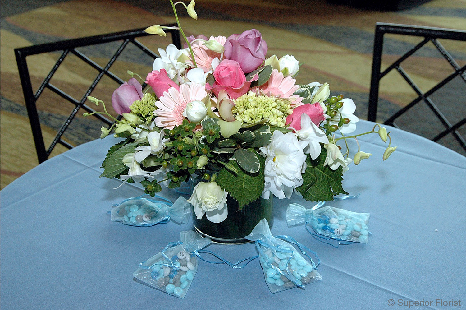 Superior Florist – Centerpieces:  Arrangement of spring colored flowers in a short, glass vase surrounded by small bags of take-home candies for guests.