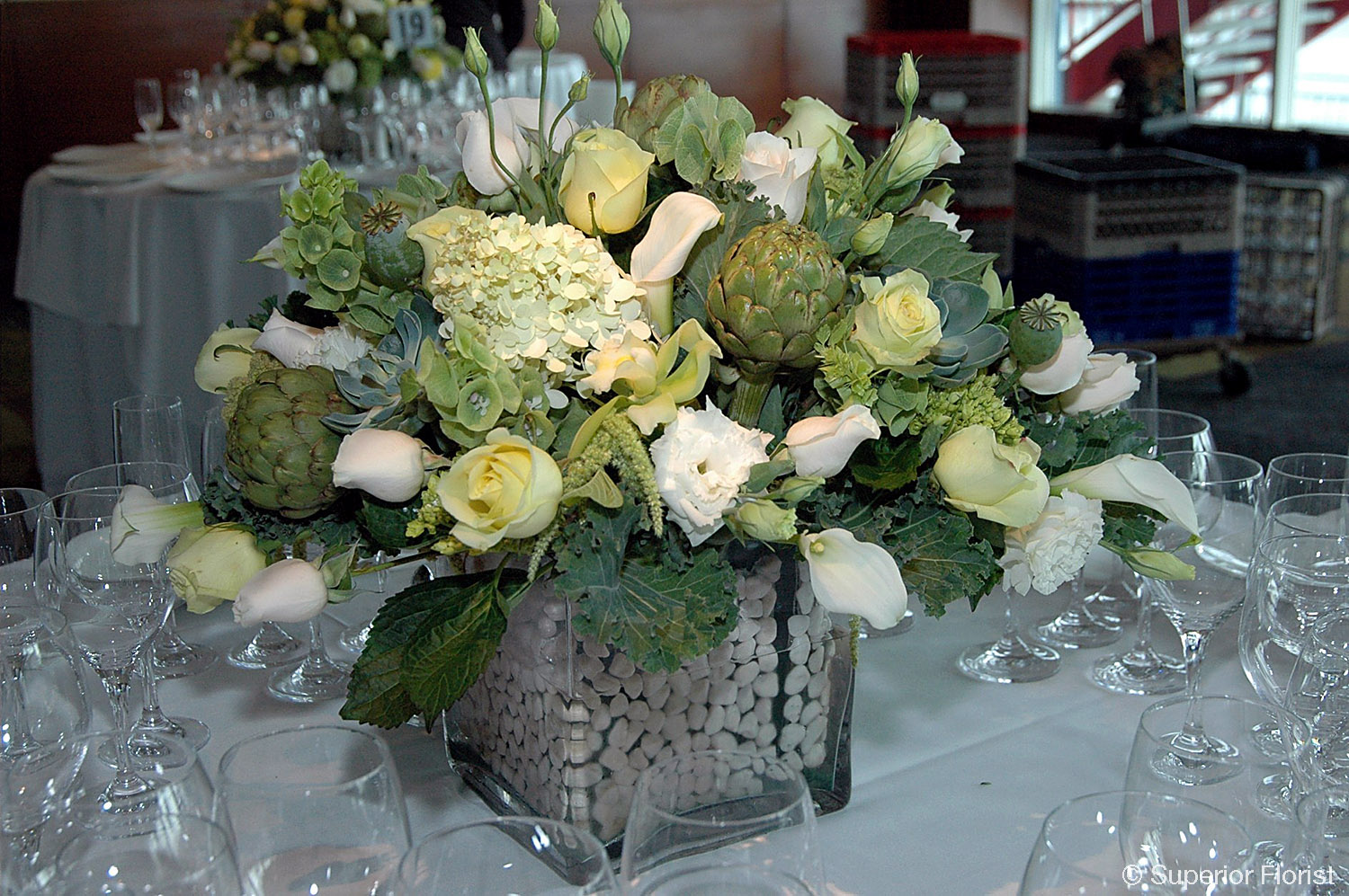 Superior Florist – Centerpieces:  Arrangement of artichokes, kale, succulents, poppies, white and green roses, mini white Callas, white Lisianthus and Bells of Ireland arranged in a large, clear, glass cube vase lined with natural stones.