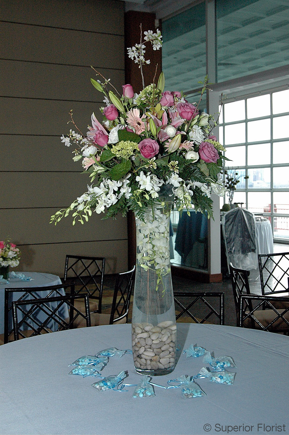 Superior Florist – Centerpieces:  Spring colors of whites pinks and lavenders in a clear glass, fluted vase. Small bags of take-home candies for guests surround the arrangement.