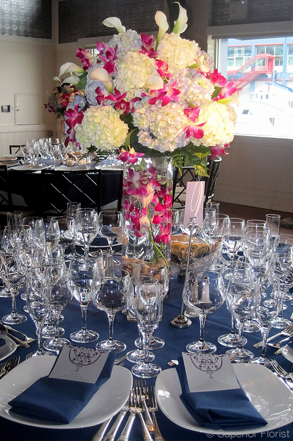 Superior Florist – Centerpieces:  Large arrangement of white and light blue Hydrangeas, Dendrobiums and Callas on top of a clear glass, cylinder vase. Submerged orchids and river rocks inside of vase.