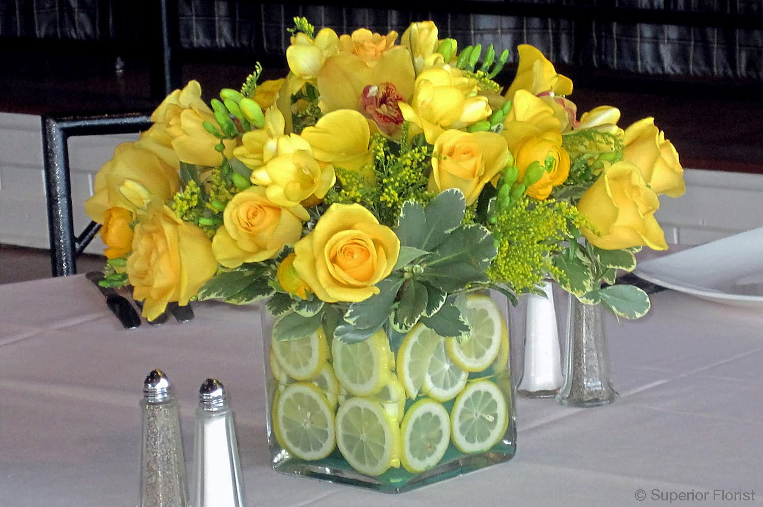 Superior Florist – Centerpieces:  Freesias, Ranunculus, Cymbidiums and roses arranged in a glass cube vase lined with lemon slices.