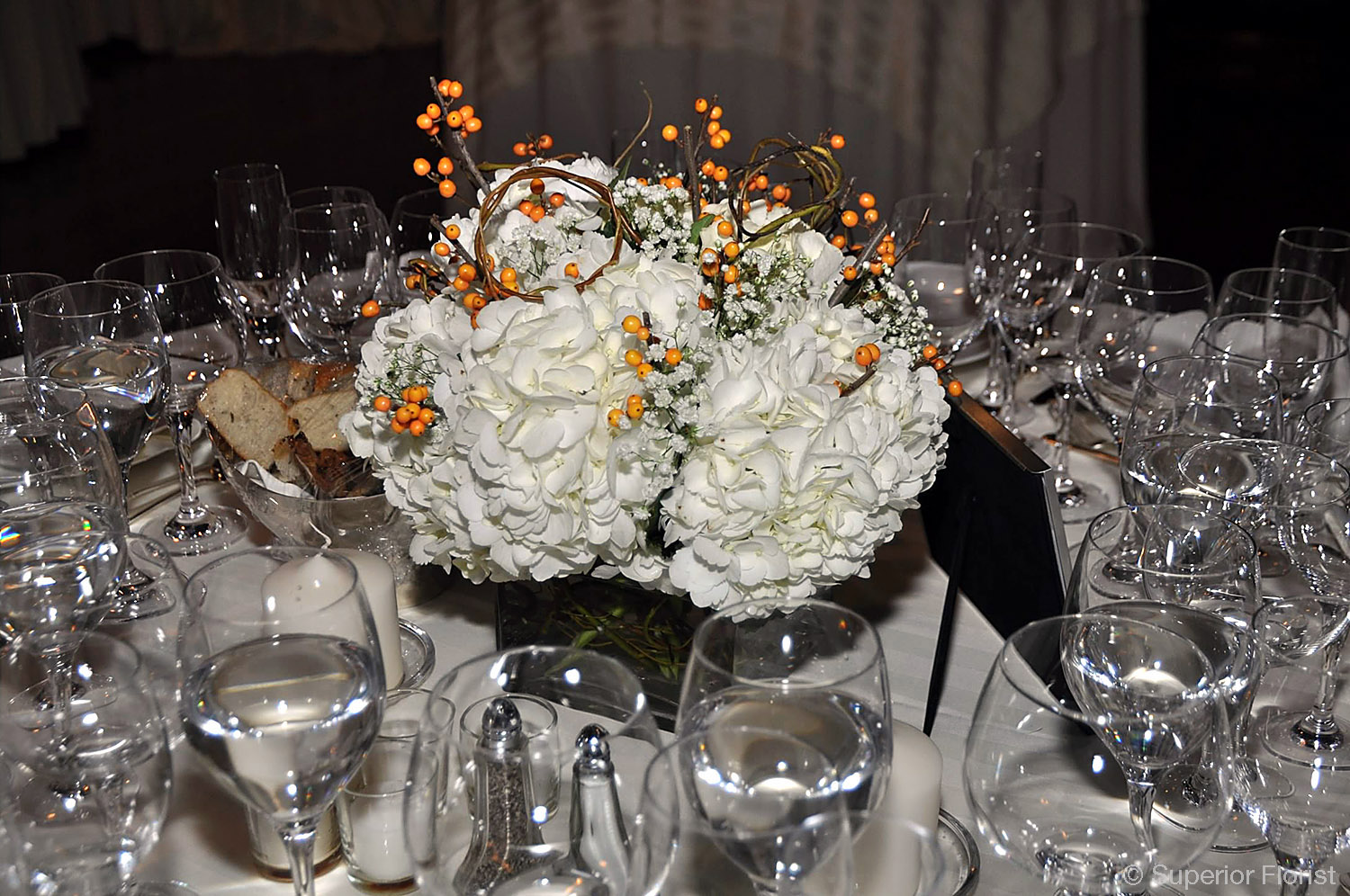 Superior Florist – Centerpieces: Dinner table centerpiece of Hydrangeas, Baby's Breath and orange ilex branches in a small, glass cube vase.