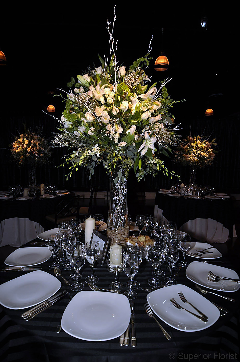 Superior Florist – Centerpieces:  Birch, Lilies, tulips, Dendrobiums, Amaryllis and roses in a fluted vase with submerged white and silver birch. New Year's Eve wedding. The Lighthouse at Chelsea Piers, NYC.