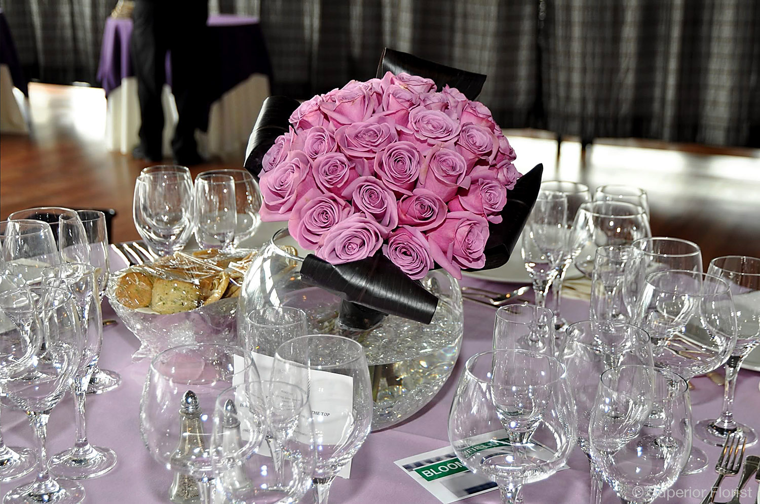 Superior Florist – Centerpieces:  Angled cluster of lavender roses and folded Ti leaves. Large fish bowl vase with clear, glass gems in bottom.