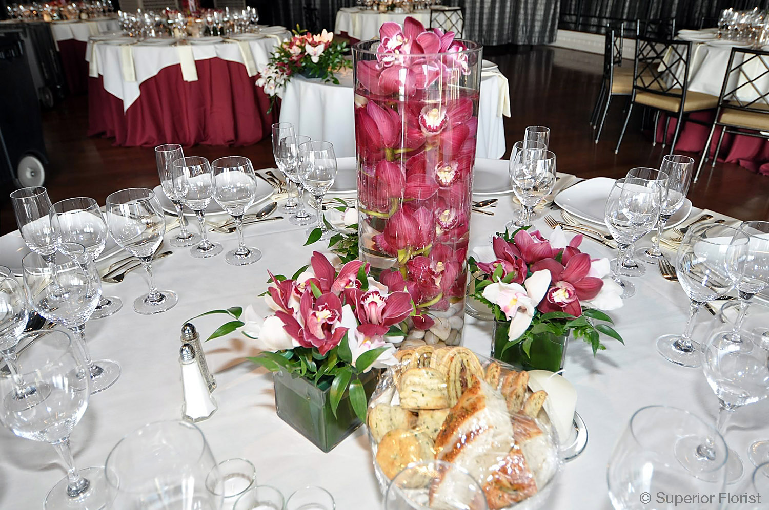 Superior Florist – Centerpieces: Submerged Cymbidium orchids in a clear glass, cylinder vase with river rocks in base. Three smaller arrangements of Cymbidium orchids around main arrangement (two in front and one behind).
