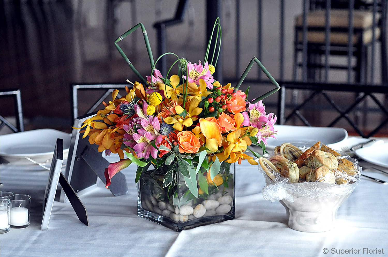 Superior Florist – Centerpieces:  Callas, Alstroemerias, Mokara orchids, spray roses, thistle, Craspedias, Hypericums, steel grass and Equisetums (aka horse tail). Glass, cube vase with river rocks in base.