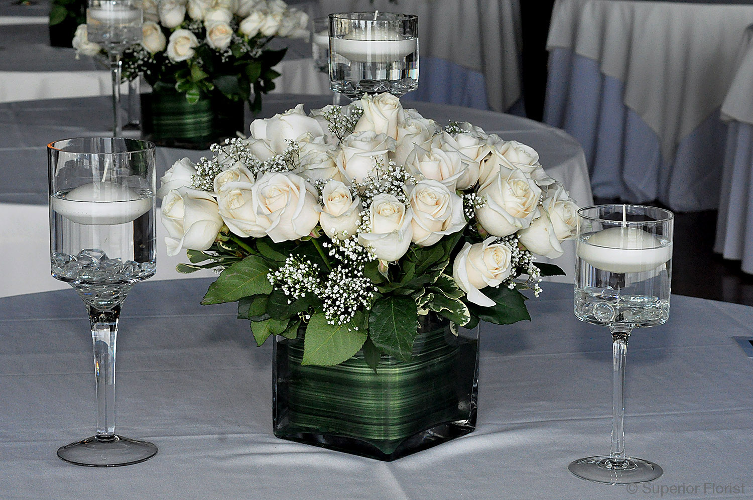 Superior Florist – Centerpieces:  All white roses, Baby's Breath and greens in a glass cube vase lined with leaf wrap. Arrangement complemented by three candleholders each with floating candles.