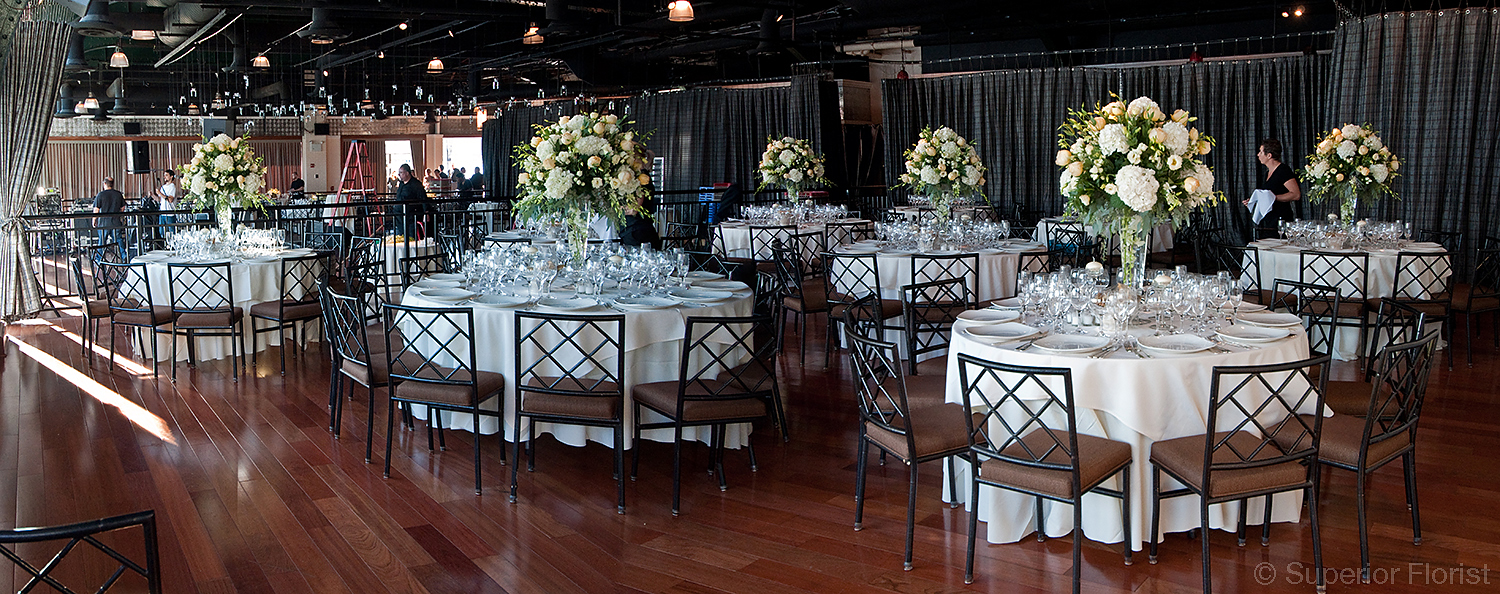 Superior Florist – Centerpieces:  Large table centerpieces of an assortment of all white flowers. In background, votives suspended above dance floor. The upper tier at The Lighthouse at Chelsea Piers, NYC.