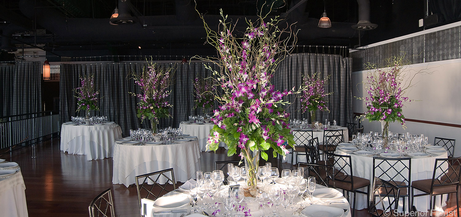 Superior Florist – Centerpieces:  Tables with tall arrangements of curly willows, variegated Dendrobium orchids and tropical foliage. Upper tier of The Lighthouse at Chelsea Piers, NYC.