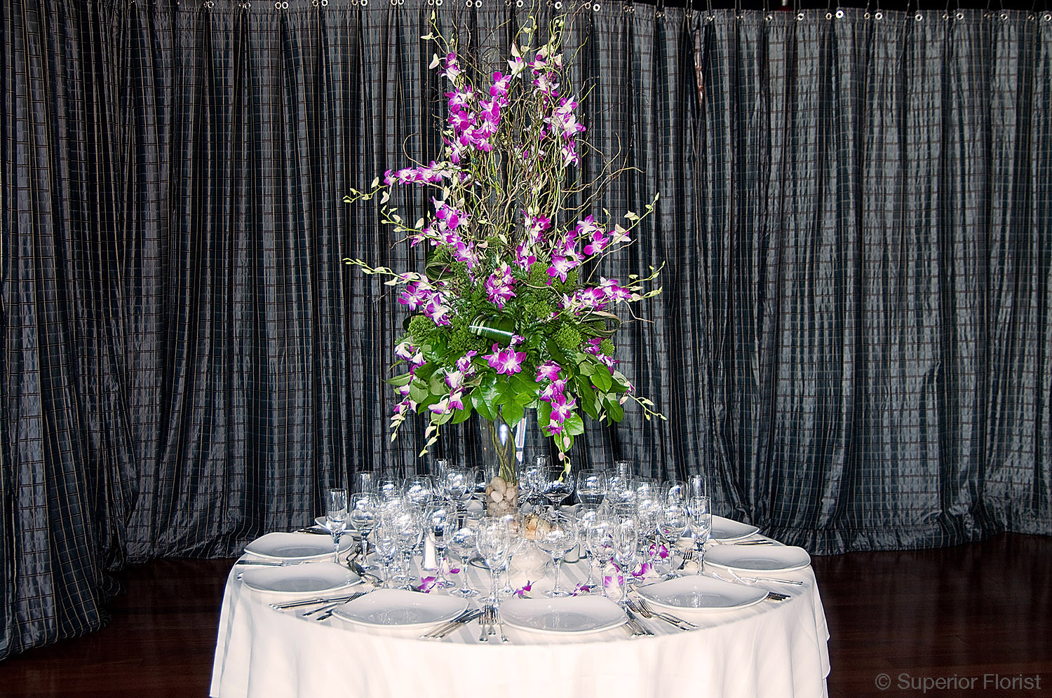 Superior Florist – Centerpieces:  Tall arrangement of curly willows, variegated Dendrobium orchids and assorted foliage in a trumpet vase.  River rocks in vase bottom.