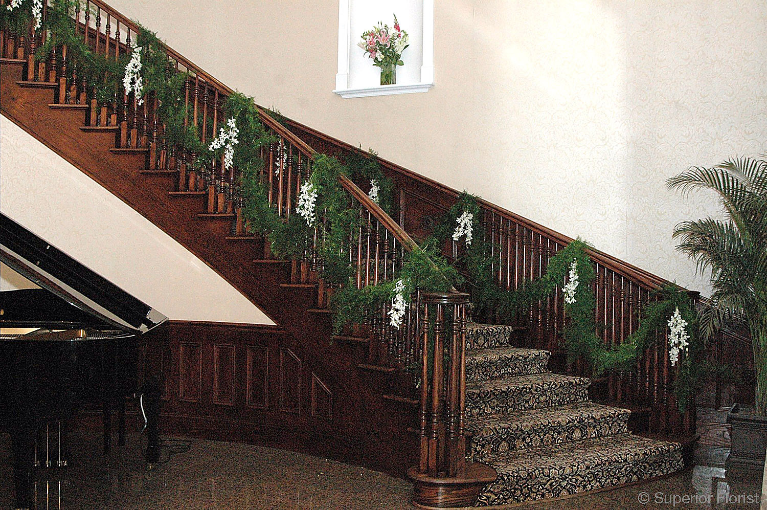 Superior Florist – Wedding Décor:  Staircase banister decorated with garland of greenery and swags of Dendrobium orchids.