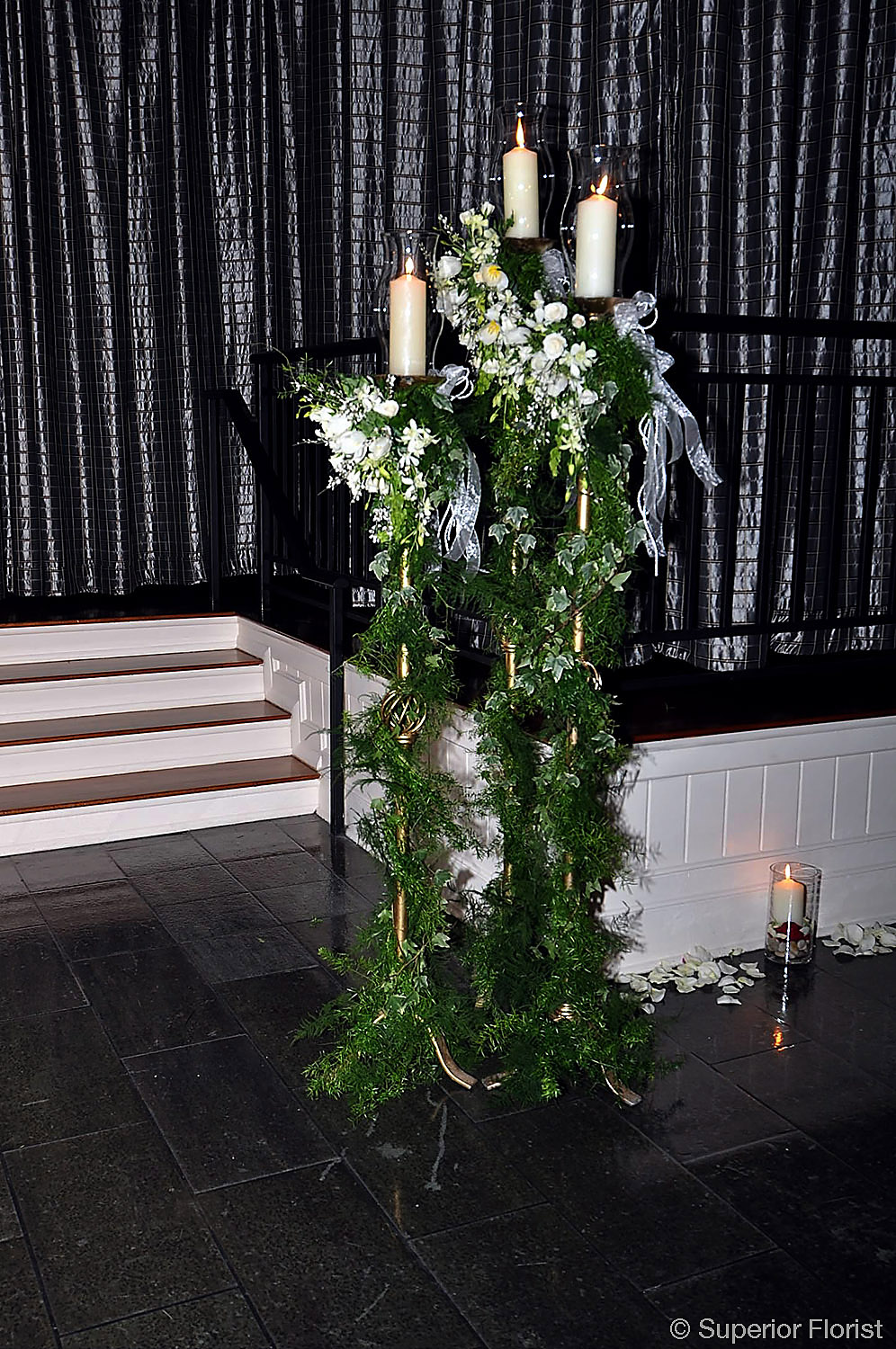 Superior Florist – Wedding Décor:  Wrought iron pillar candle stands (graduated sizes) with hurricane lamps decorated with greenery and clusters of flowers. Entryway of The Lighthouse at Chelsea Piers, NYC.
