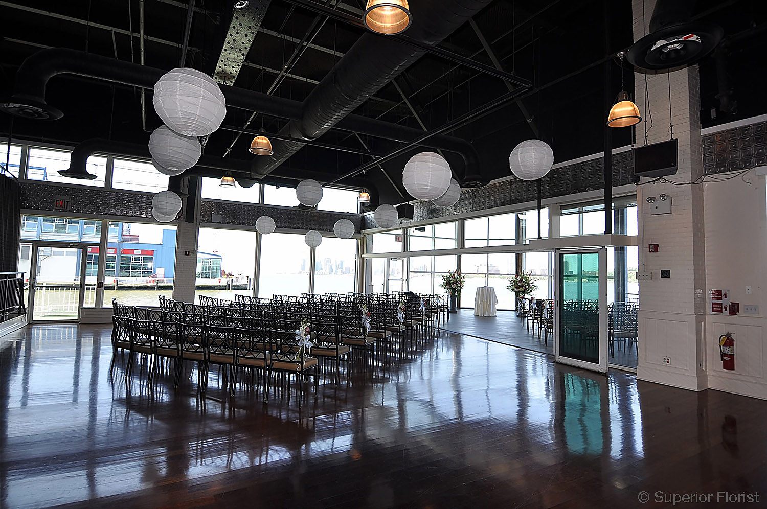 Superior Florist – Wedding Décor:  Lanterns suspended over dance floor. Seating area for wedding guests in background. The Lighthouse at Chelsea Piers, NYC.