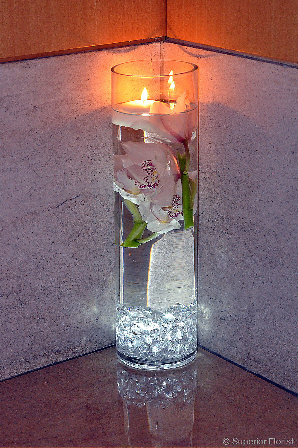 Superior Florist – Wedding Décor:  Clear glass cylinder vase with floating candle and submerged Cymbidium orchids.