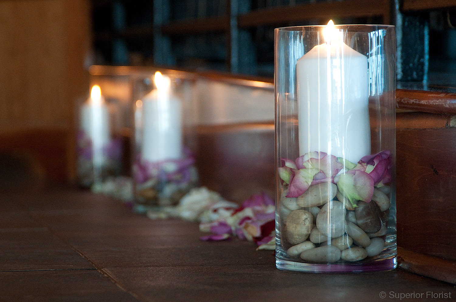 Superior Florist – Wedding Décor:; Pillar candles in glass vases with river rocks and rose petals.