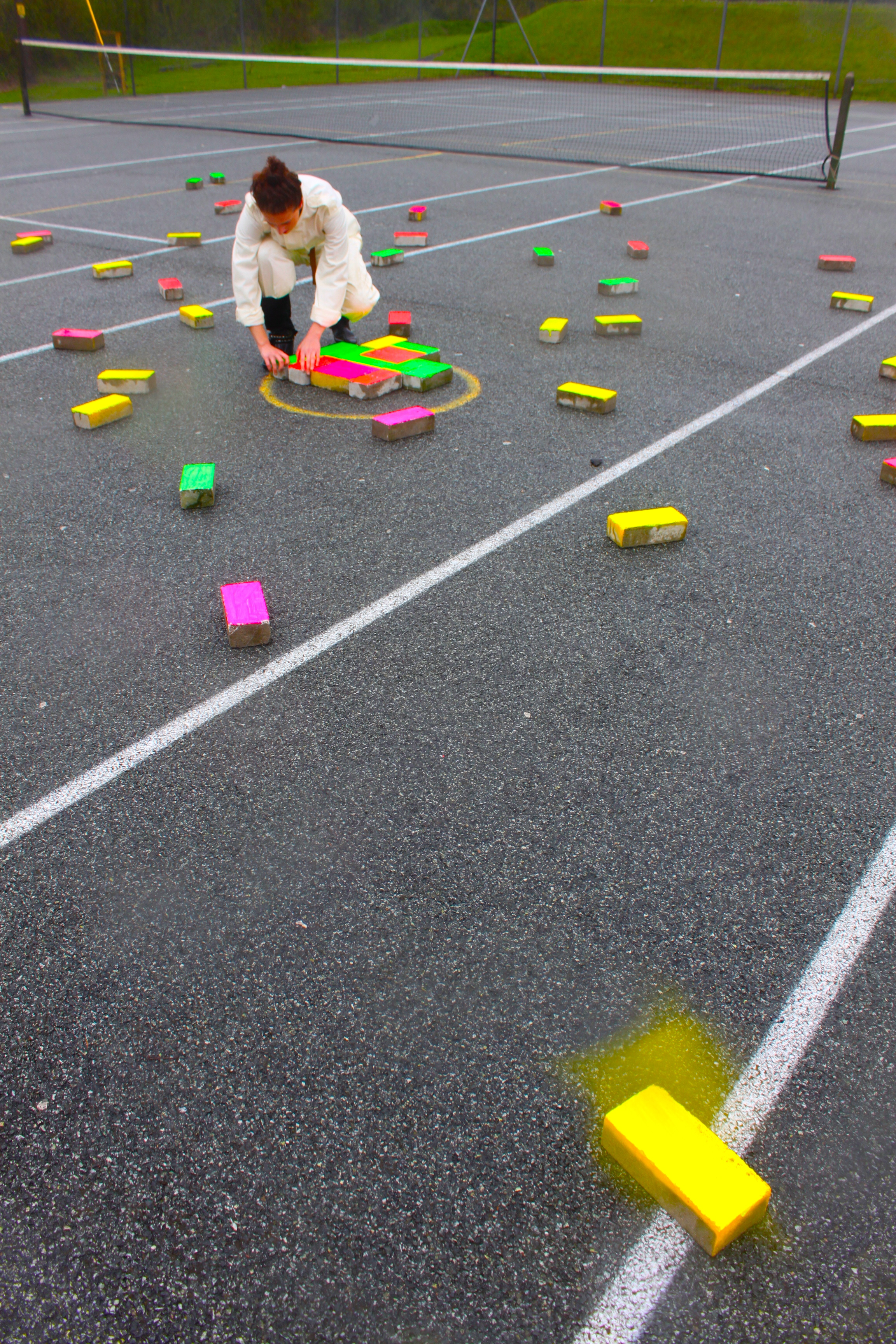 Ticker-Tape: Playground - PerformanceTicker-Tape: Playground occurred at Ysgol Gyfun Emlyn/Newcastle Emlyn Secondary School in Wales at 11:20am on Thursday 9.5.13. The artist stacked 100 bricks in the centre of the caged tennis court before silently placing the fluorescent bricks on the floor so that they appeared like confetti scattered across the playground.Students watched from windows and doorways. The playground is a socially significant space;Govier commented: