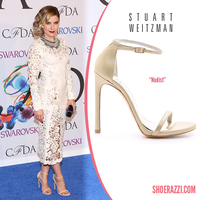 Credit: Andres Otero/Wenn   Sophia Bush  wore  Stuart Weitzman   Nudist  sandals to the 2014 CFDA Fashion Awards held at Alice Tully Hall in London. They feature nude leather, thin adjustable ankle-strap and 4.5″ stiletto heel.  Nudist  is available in several styles at  Stuart Weitzman .   Outfit Details : Marchesa Fall 2014 ivory laser cut long sleeve dress with a scalloped hemline, spiral curled locks, Dannijo  Norgaard  bib necklace , ice-blue Rauwolf oval cut clutch and a romantic ruby red lip.