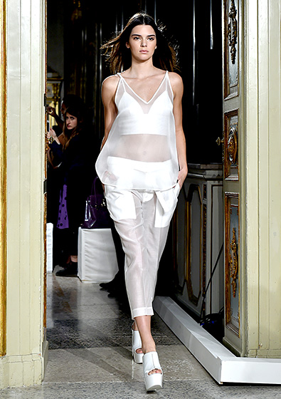 Credit: Stefania D'Alessandro/Getty Images   White-hot! Jenner bared a peek of her toned abs in a sheer white top and matching pants for the Ports 1961 show on Sept. 18.