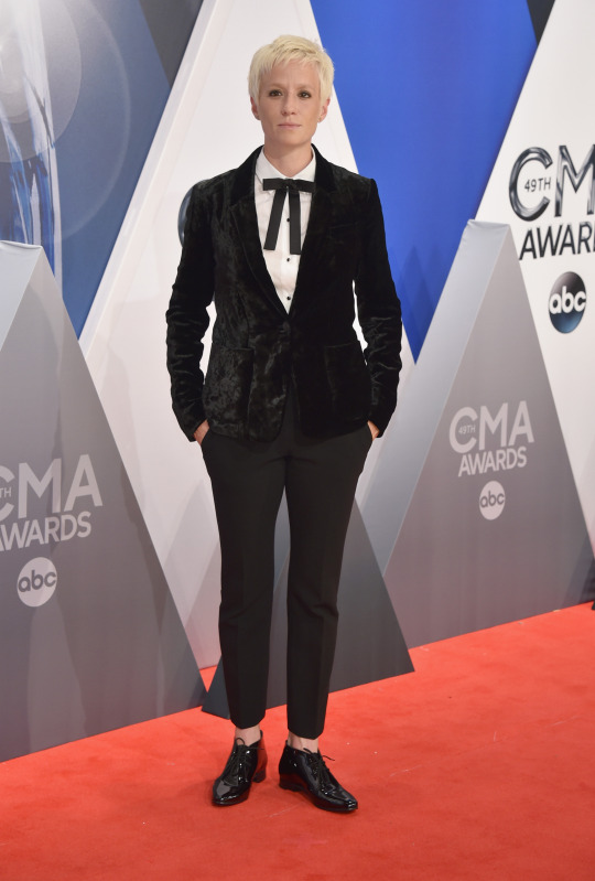 Megan Rapinoe in a black velvet blazer, bowtie, and slacks.   This professional soccer player knows how to rock a suit. Rapinoe looked extra sharp in a velvet blazer (VERY fall 2015!) with a white shirt underneath and a cute bowtie tied at the collar. It was a playful addition to an outfit that could have otherwise been   to an outfit that could have otherwise been a bit dull.