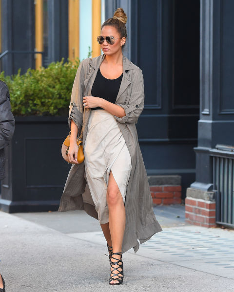 In a sheer duster coat, cream slit skirt and lace-up heels.  SPLASH