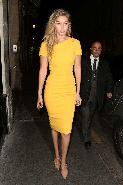 Out to dinner in Paris wearing a yellow Victoria Beckham sheath dress and nude pumps.  GETTY
