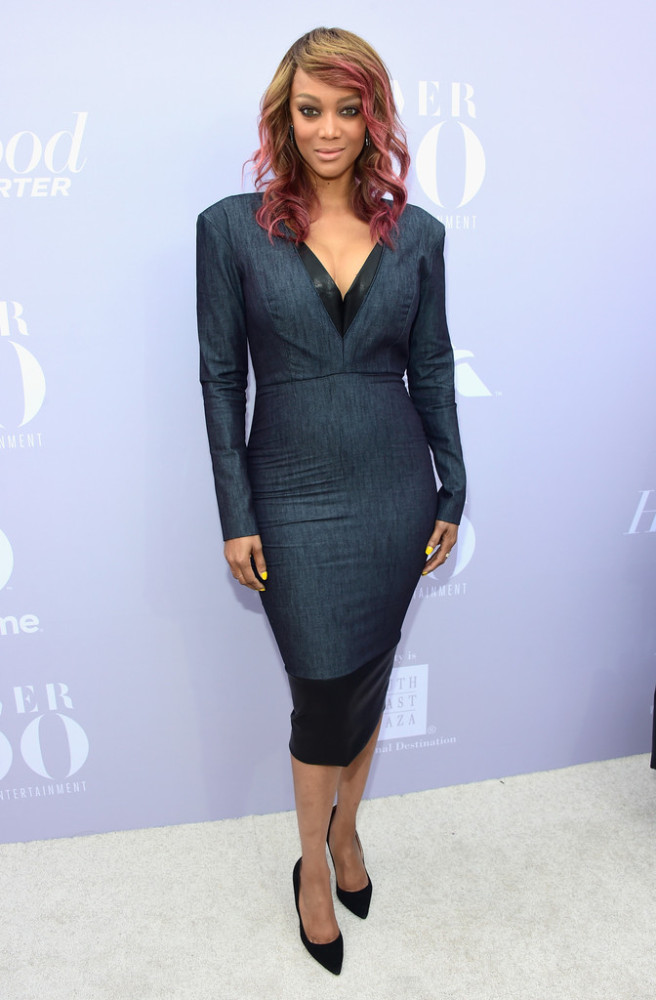 Tyra Banks flaunted her curves and new pink highlights in a denim and black leather figure-hugging number.