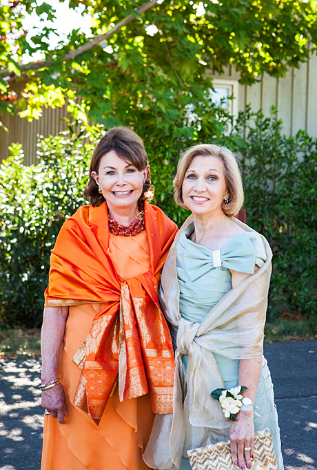 "Dare and Garrick's formal ""California casual-meets-Old South"" wedding took place at the Carneros Inn in Napa, California. The mothers of the bride and groom posed for this adorable photo in their festive, tiered dresses and shawls. The mother-of-the-bride's vibrant coral dress was purchased from Wilkes Bashford boutique in San Francisco.    See more orange mother-of-the-bride dresses.      View more photos from Dare and Garrick's wedding.    Photo:  Kate Webber Photography"