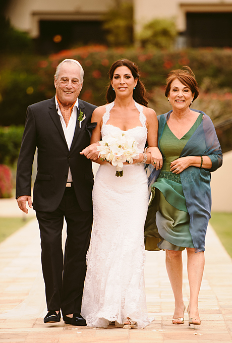 Jessica and Matthew jetted off to Hawaii for their romantic destination wedding at the Four Seasons Resort Maui at Wailea. Both of the bride's parents escorted her down the aisle for the outdoor ceremony, and the mother of the bride's green Donald Deal dress with its blue shawl was a subtle call-out to the colors of the surrounding Pacific Ocean.  See more green mother-of-the-bride dresses.  View more photos from Jessica and Matthew's wedding.  Photo: Ashley Camper