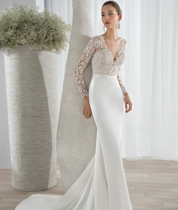 This sleek luxe satin sheath gown features a lace bodice with a plunging V-neckline and long lace sleeves. Transitioning to a high back with button closures and a sophisticated Chapel length train.    Available Colors: Ivory/Nude/Natural, White/Nude/Natural, Ivory/Natural, White/Natural, Ivory/Nude, White/Nude, Ivory, White  View Size Chart