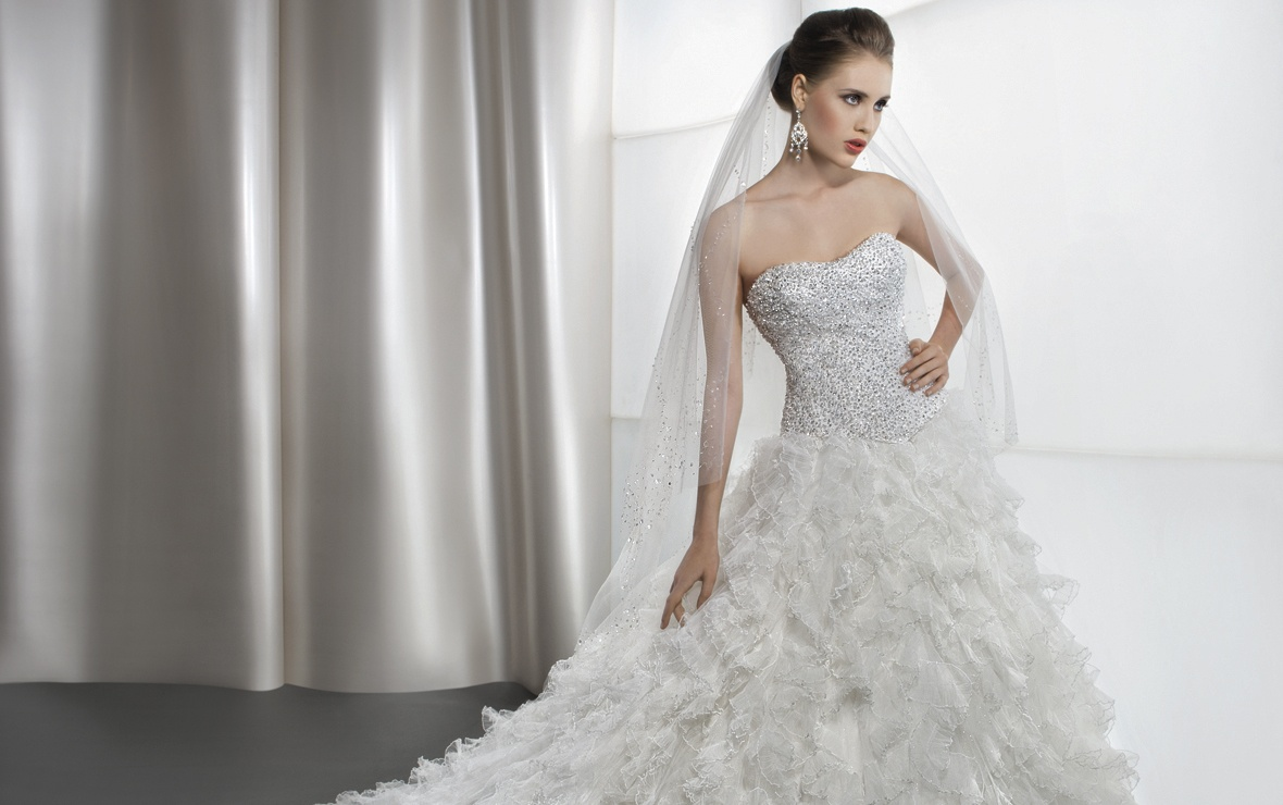 Shimmering, strapless bridal gown with a soft, sweetheart neckline and basque waist. This wedding dress features a full A-line skirt with layers of ruffled, pleated tulle and an attached train.    Available Colors: White, Ivory  View Size Chart