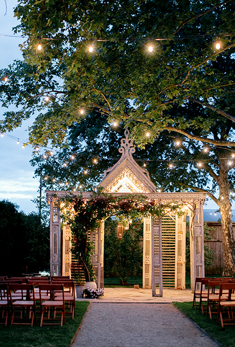 Red flowers and greenery climb up this white wooden arbor for a romantic, vintage look.  Photo:  Emily Wren Photography