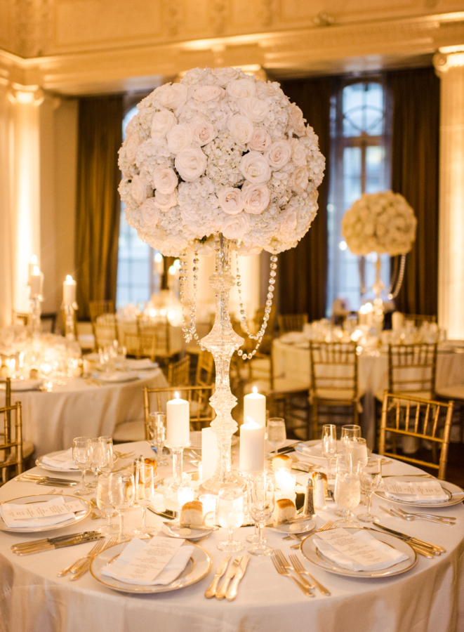 "From  Rebecca Yale Photography … Chanel and Adam's gorgeous wedding day was truly magical in every way. Not only was the day full of love and happiness, but every detail had been thoroughly thought out and planned to perfection. The classic Yale Club venue set the scene for a day of elegance and glamour. Diana Gould Ltd decked out the room in gorgeous white roses dripping in crystals and made even more romantic by the hundreds of candles scattered across the tables bathing the room in a warm yellow glow straight out of a fairy tale. The tables were named after cities the bride and groom visited together and their calligrapher Christina DellaValle created a custom drawing of the city for each table. The bride wore a stunning lace and tulle ballgown designed custom for the bride by the bride's mother and was topped off by a sparkling head piece by Enchanted Atelier. The bride truly looked royal and while taking portraits in Central Park we were approached by many an onlooker asking if the bride and groom were celebrities!    The wedding was a real New York celebration starting of the day at the famous Plaza Hotel where the ladies got all dolled up while wearing their custom bridesmaids robes and ""Chanel"" t-shirts in honor of the bride's namesake before heading off to a beautiful ceremony at the Church of our Saviour. After the couple said their I Do's we headed north to the Central Park Conservatory Gardens for portraits in the park. The landscaped and romantic gardens were the perfect setting for photographs of their elegant black tie wedding party. The party continued over at the Yale Club where guests enjoyed champagne and hors d'ouerves on the balcony before being welcomed into the ballroom for a night of dinner and dancing."