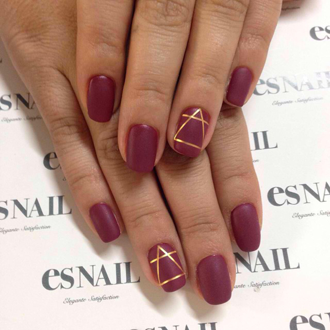 A scarlet manicure with a geometric gold detail.  Photo: es Nail via  Instagram
