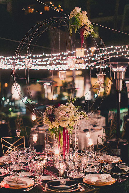 "Guests were seated at round tables that were arranged around a checkered dance floor. Each table was decorated with either black or white linens, and topped with a mix of tall, medium, and low arrangements of red and white flowers. ""Large metal orbs dripped with flowers and hanging crystals were also suspended from the overhead lighting as unique centerpieces,"" Remy says."
