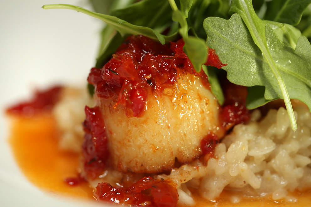 Pan-Seared Sea Scallops at Ambrosia in Eugene is plated on a bed of risotto and topped with sun-dried tomato honey glaze along with arugula. (Collin Andrew/The Register-Guard)