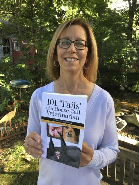 Dr. Krausman holding her book, 101 'Tails' of a House Call Veterinarian