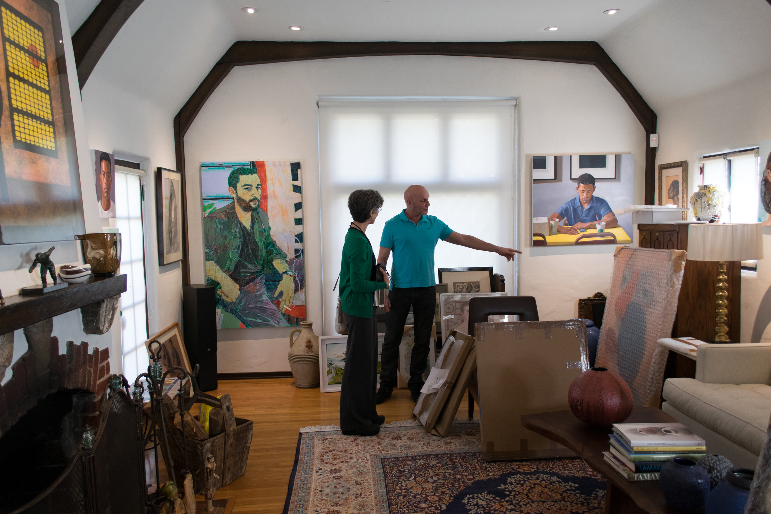 Daena Title standing next to Robert as he points to new work he has not yet unpacked.Behind on the walls are works by, at left, Hope Gangloff, and at right, Dan McCleary.