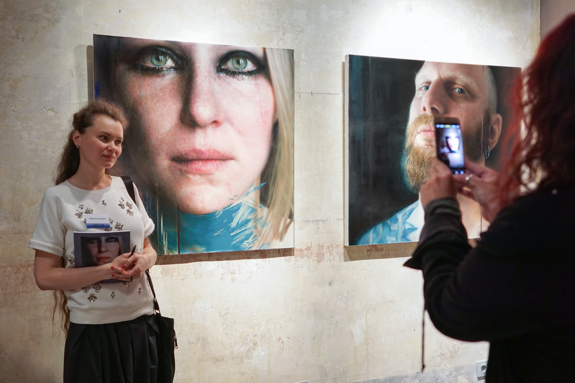 Viktoria Savenkova next to her paintings  Blue 1  (left) and  Ales  (right)