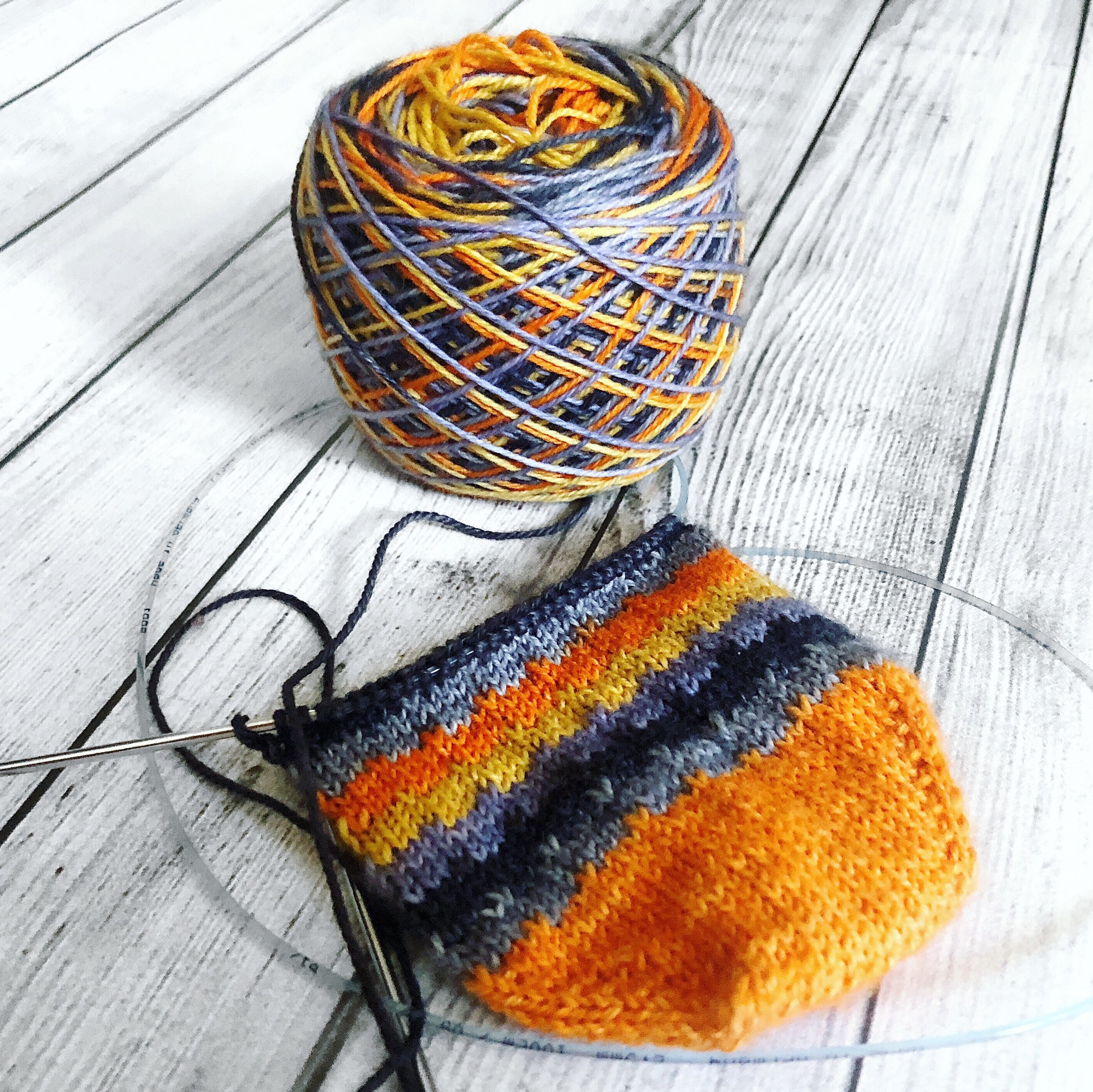 "One pair of Halloween socks I started (but never finished) knitting in The Cozy Knitter's ""Haunted"" colorway."